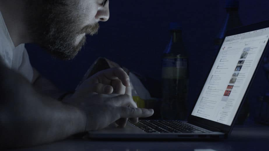 Man at night on laptop trying to hide youtube watch history and search privately