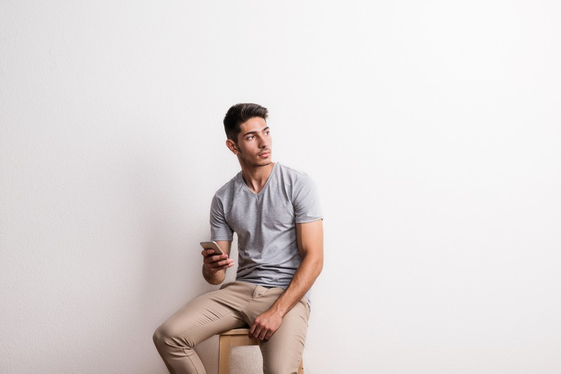 Man sitting on a stool holding a smartphone with best minimalist android launcher on it