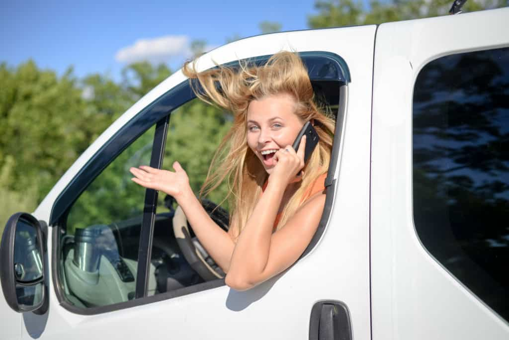 Blond driver using phone hanging out of the van window without worrying her burner phone number can be traced
