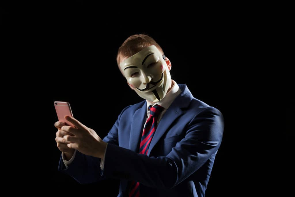 Businessman wearing a guy fawkes mask carefully using his burner phone number which can be traced