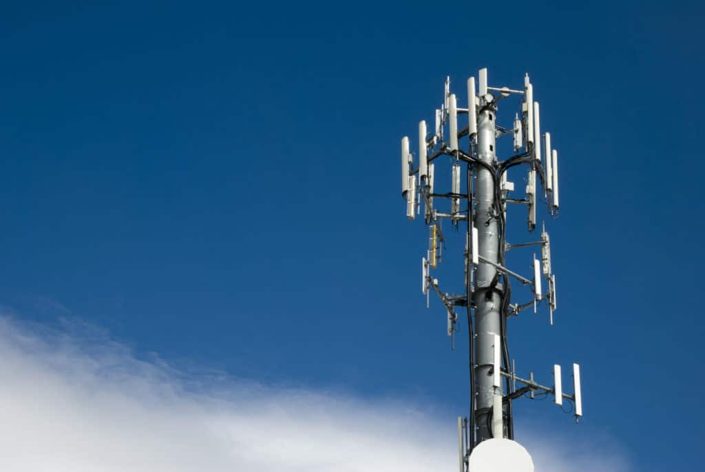 Cellular tower against a partly cloudy blue sky ready if you switch mobile data from off to on