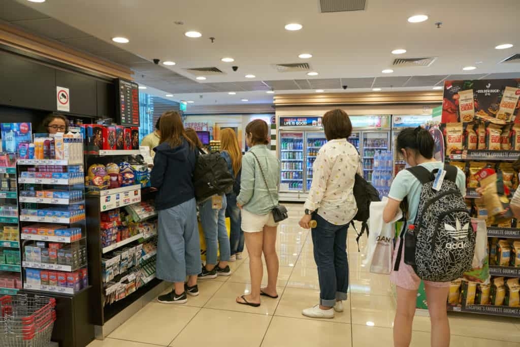 People in a convenience store line one of which is buying a burner phone number which can't be traced