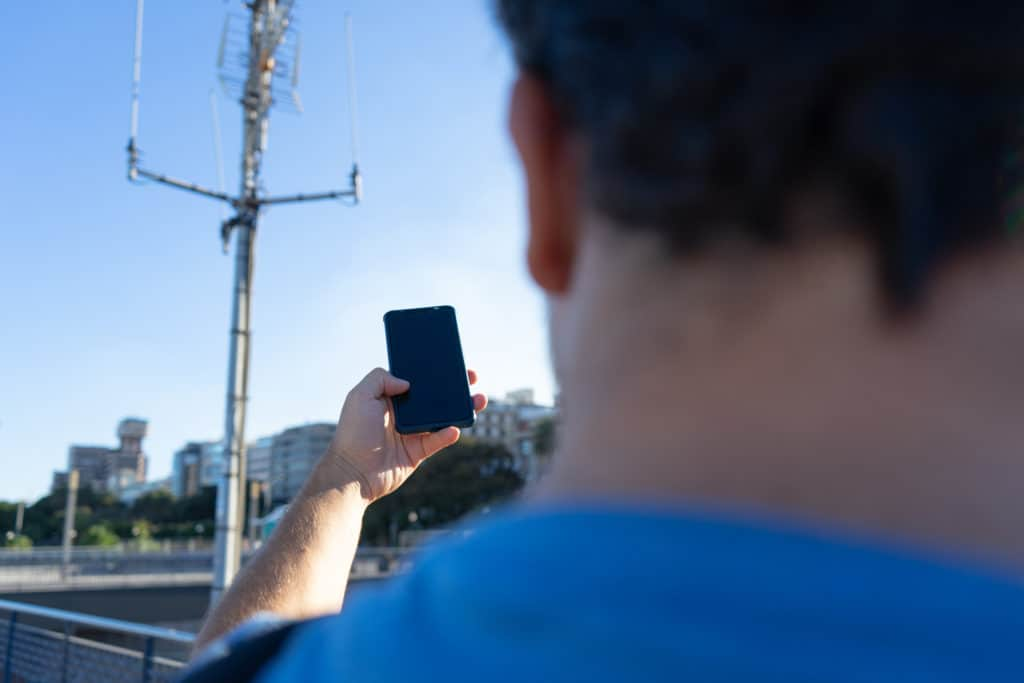 Man pointing a smartphone at a cell tower wondering if is mobile data is on or off