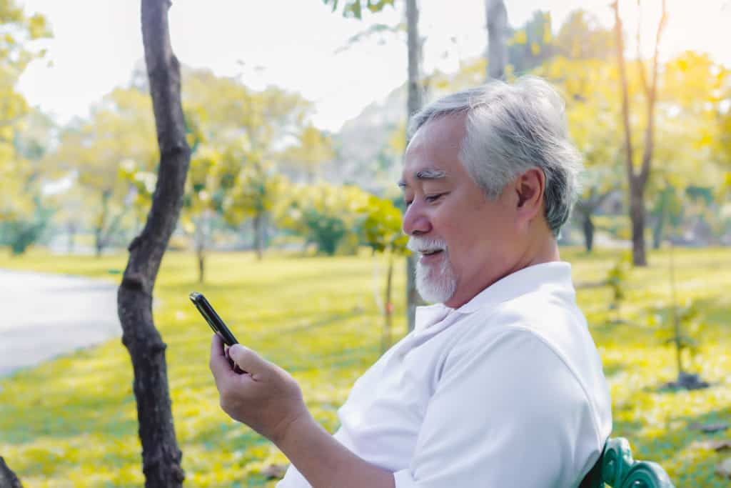 Older man in a park using his burner phone number so he can't be traced