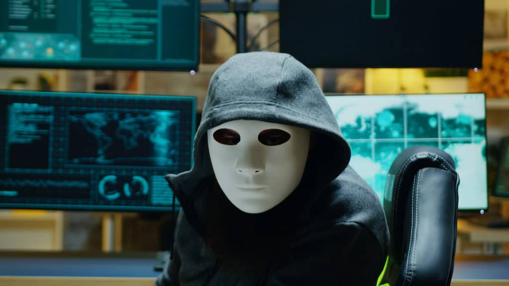 Masked hacker looking at viewer making us question: can encrypted data be hacked?
