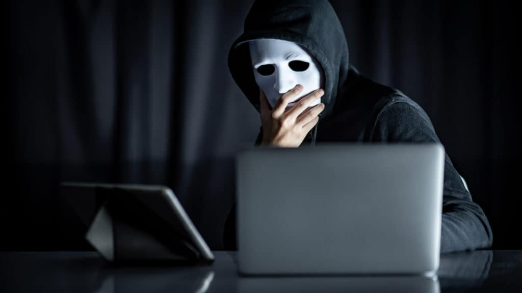 Masked hacker thinking about why you should encrypt data