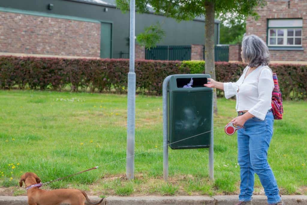 Older woman in a park throwing away her burner phone number so she can't be traced