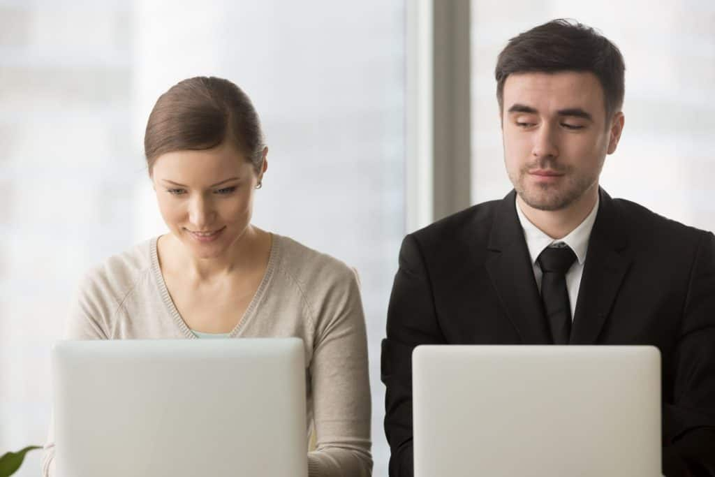 Business man looking over his colleague's laptop to see her google drive files