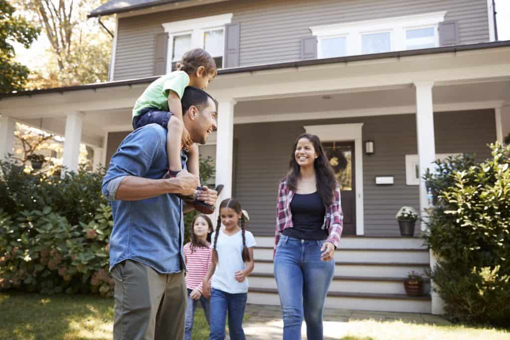 Smiling woman and her family outside their nice home that she worked hard in her cyber security job