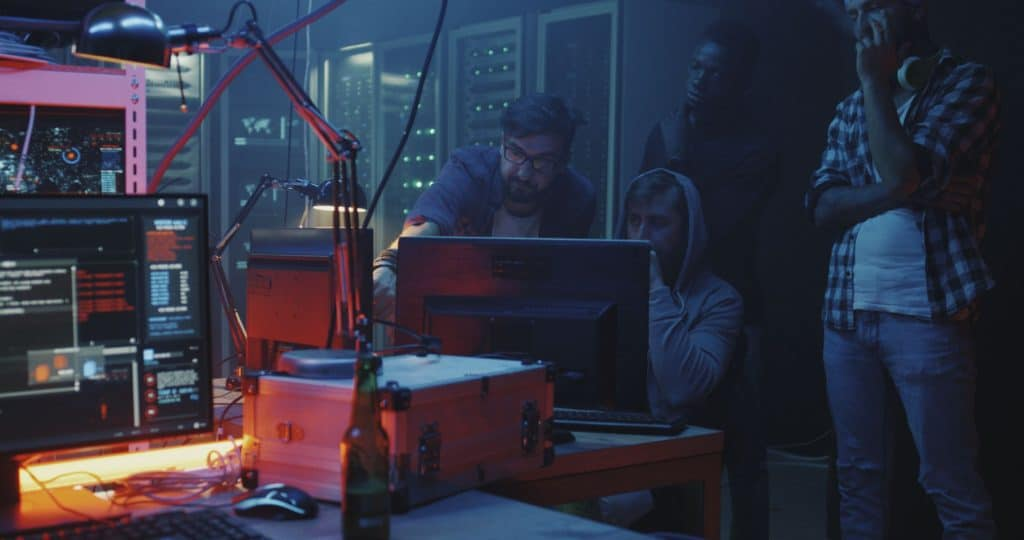 4 hackers in basement lair committing cybercrime stressing the importance of online privacy