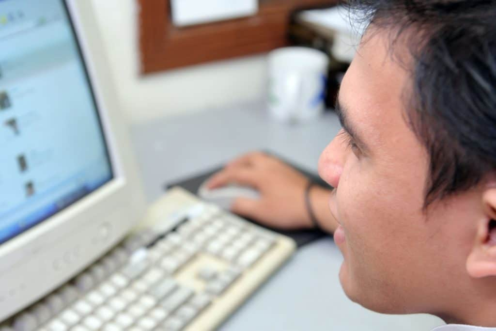 Man using 1990s computer browsing forums without worrying about the origin of cyberbullying yet