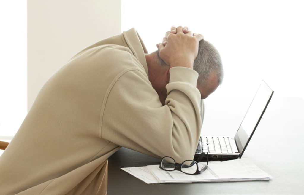 Man hands on head sadly looking down at laptop having clicked on attachment link after opening spam email