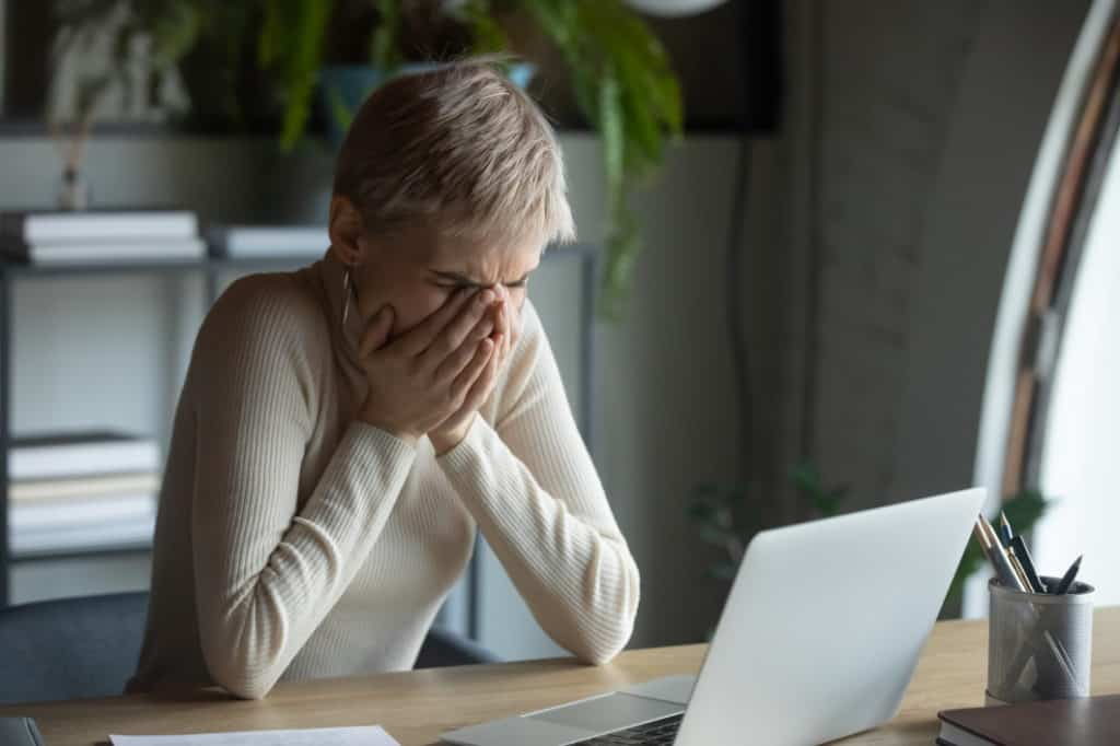 Woman with laptop covering her mouth after accidentally opened a spam email