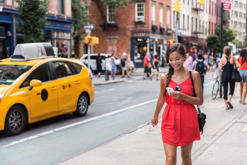 Woman walking on city street with smartphone smiling that wifi helps location accuracy