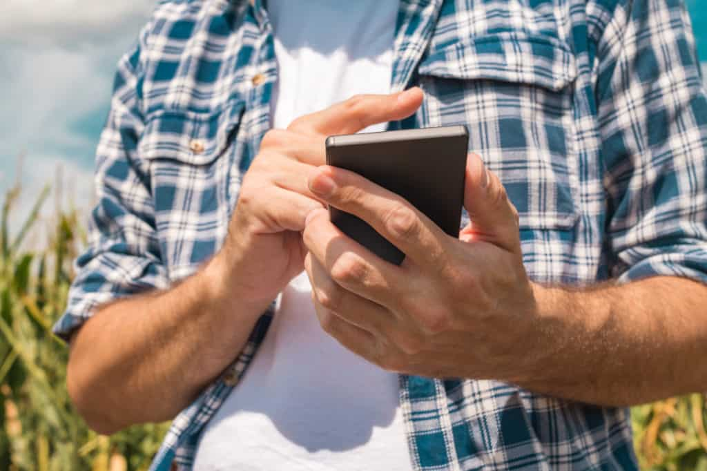 Man holding smartphone texting wondering if it's sent over wifi