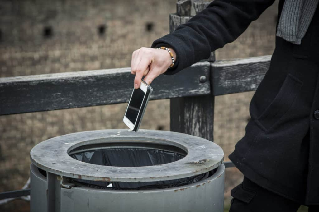 Person dropping burner smartphone into trash to protect his phone number