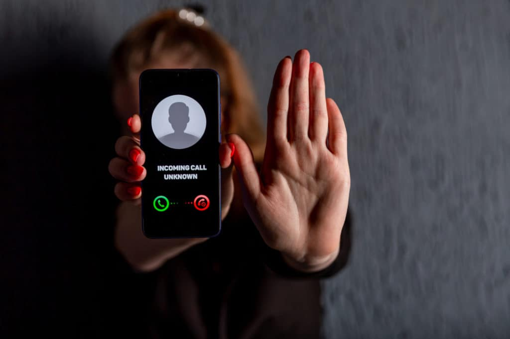Woman holding her hand up with to unknown caller trying to protect her phone number