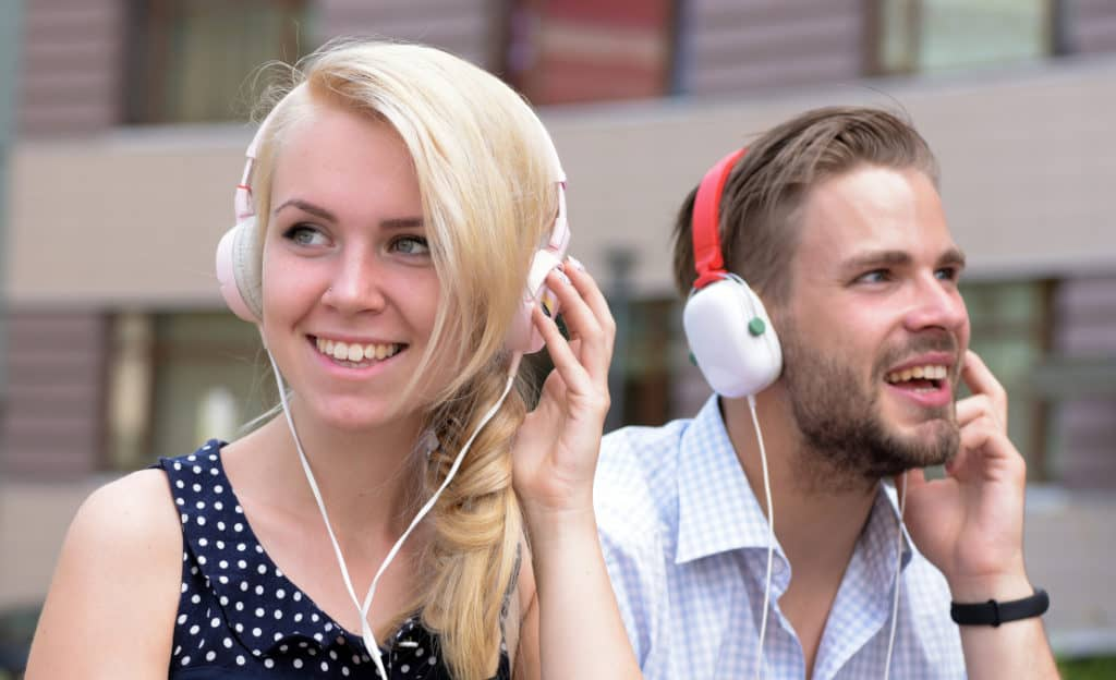 A couple wearing wired headphones instead of using a bluetooth router or hub