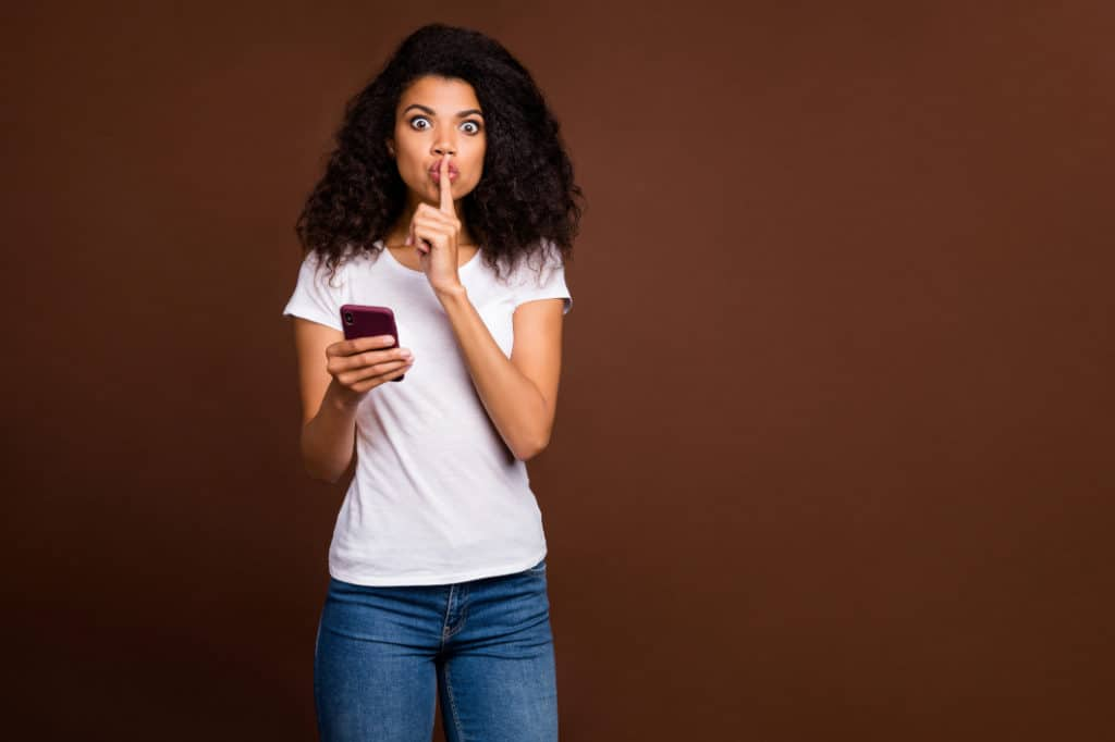 Woman holding smartphone with finger on lips since she knows how to hide numbers on your phone bill