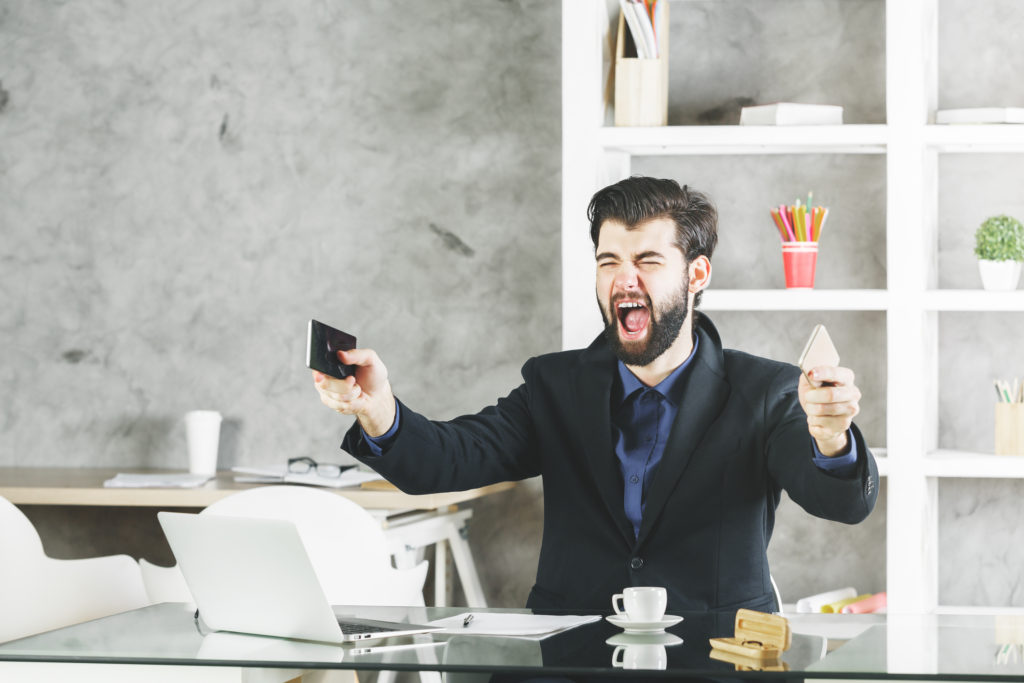 Businessman at his desk holding both his personal and work phone while yelling