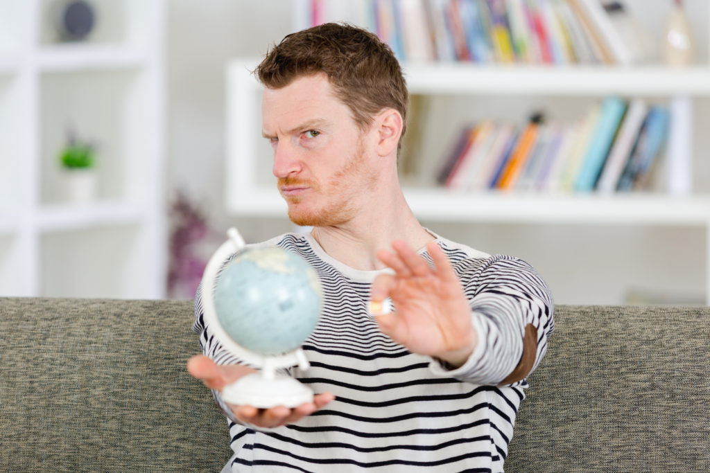 Man holding a globe and sim chip with questioning look wondering if you can use a phone without a sim card
