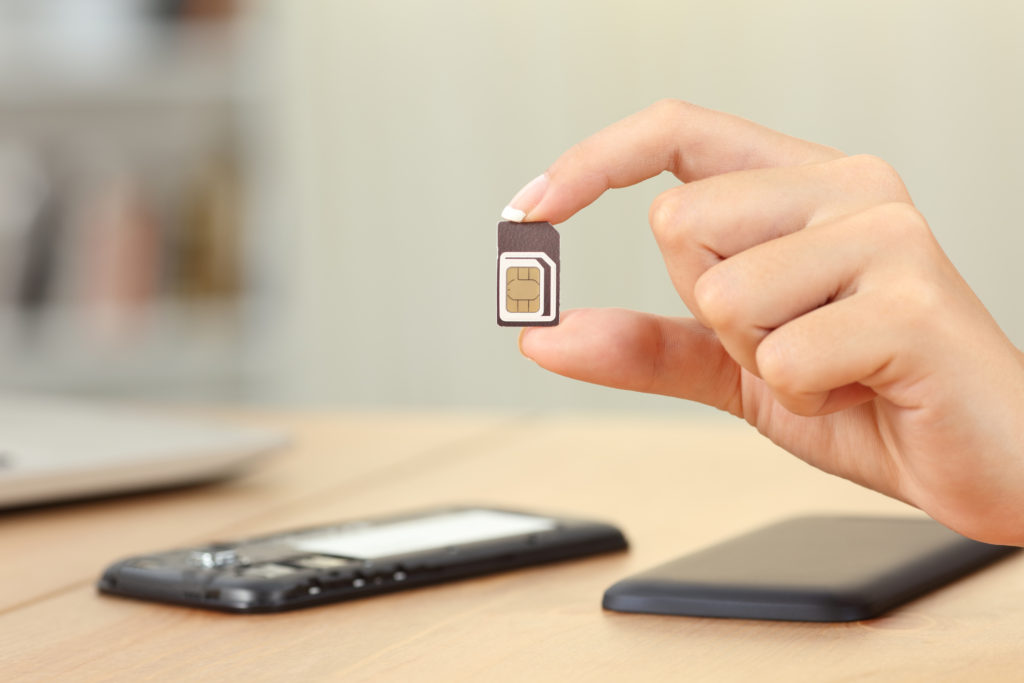 Woman's hand holding a sim chip leaving her to wonder if you can use a phone without a sim card
