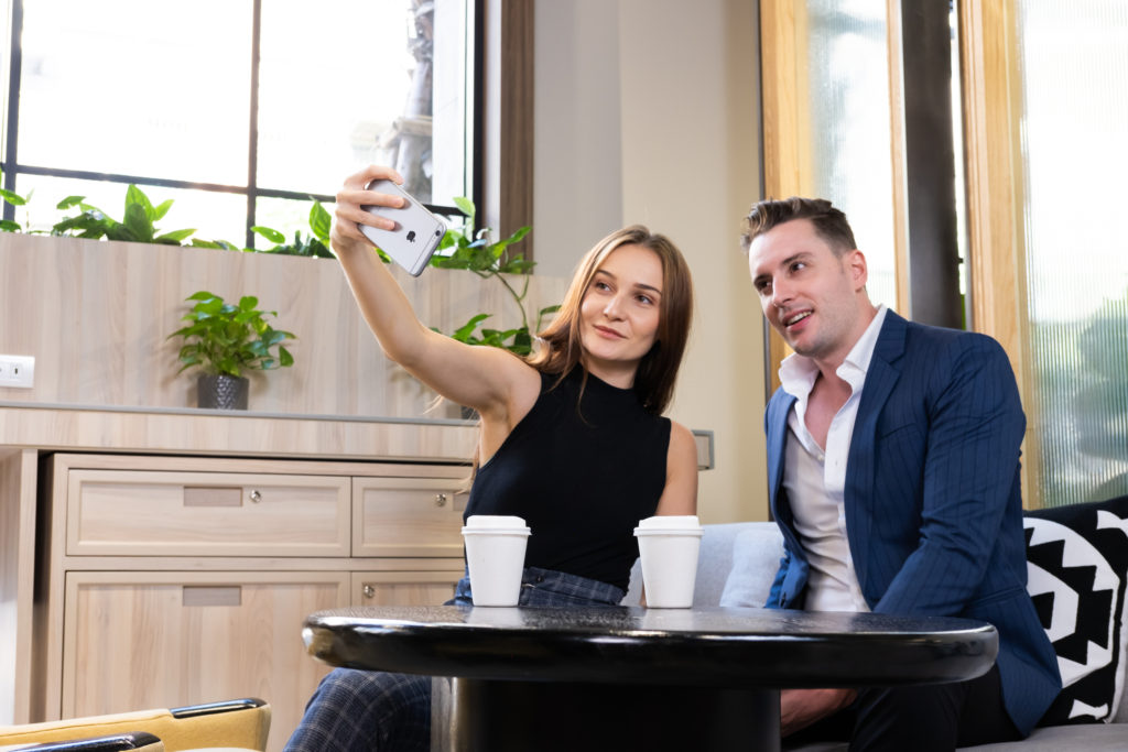 Couple at coffee shop taking selfie because dating apps are social media