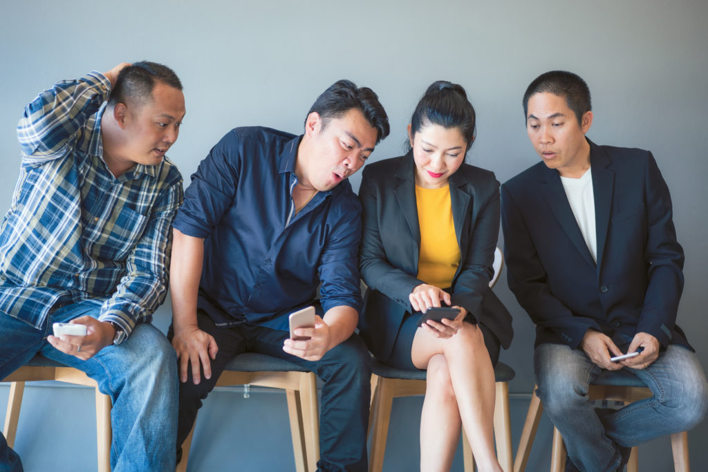 Three male friends helping their female friend with her dating social media app