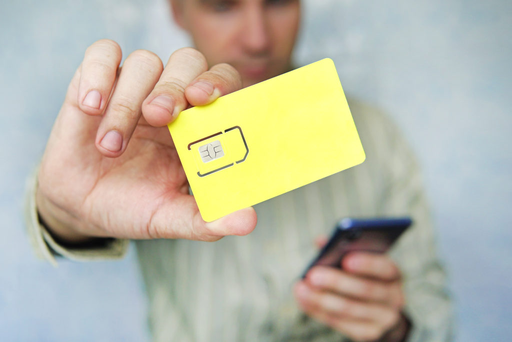Man hold smartphone and sim chip hoping he can have a new sim card with the same number