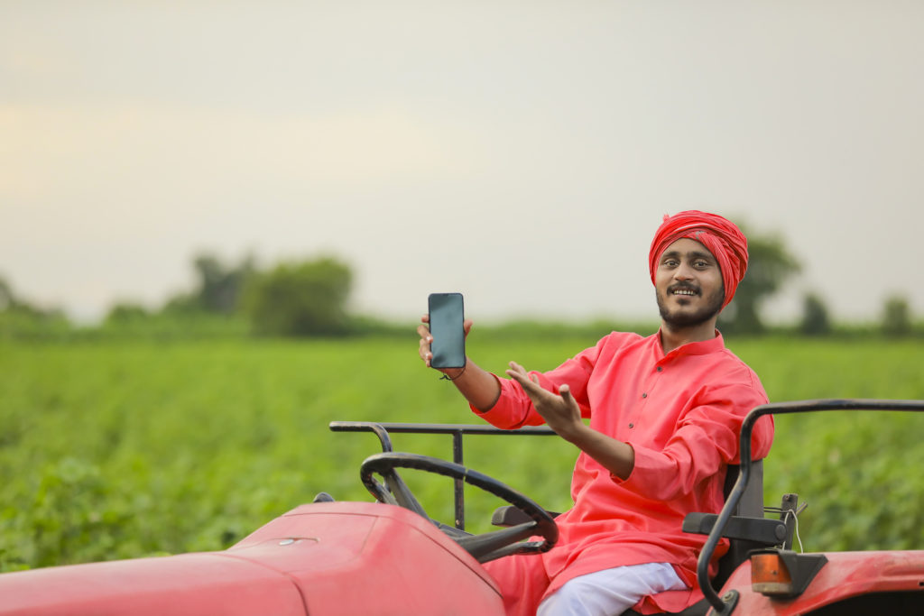 Indian farmer holding smartphone on tractor knowing he's using a safe alternative to mms