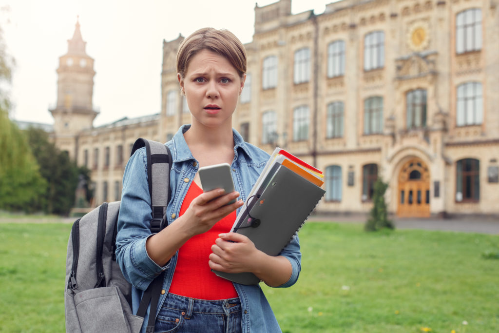 Student at university holding smartphone concerned: is mms safe any more
