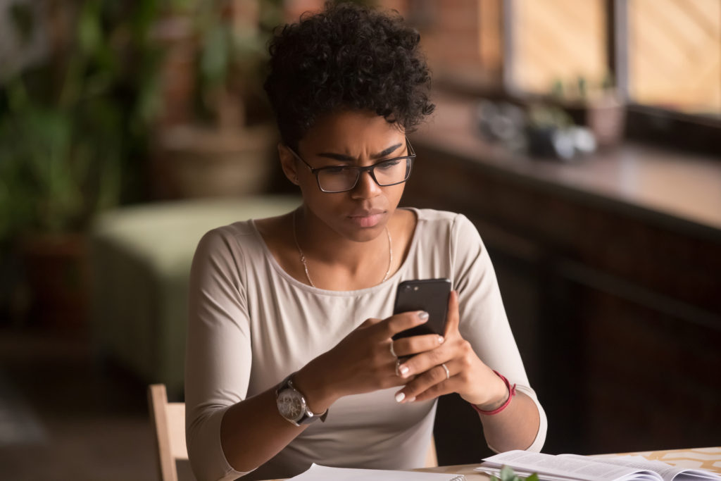 Worried woman holding smartphone having received an sms and wondering: can a text be traced or tracked.