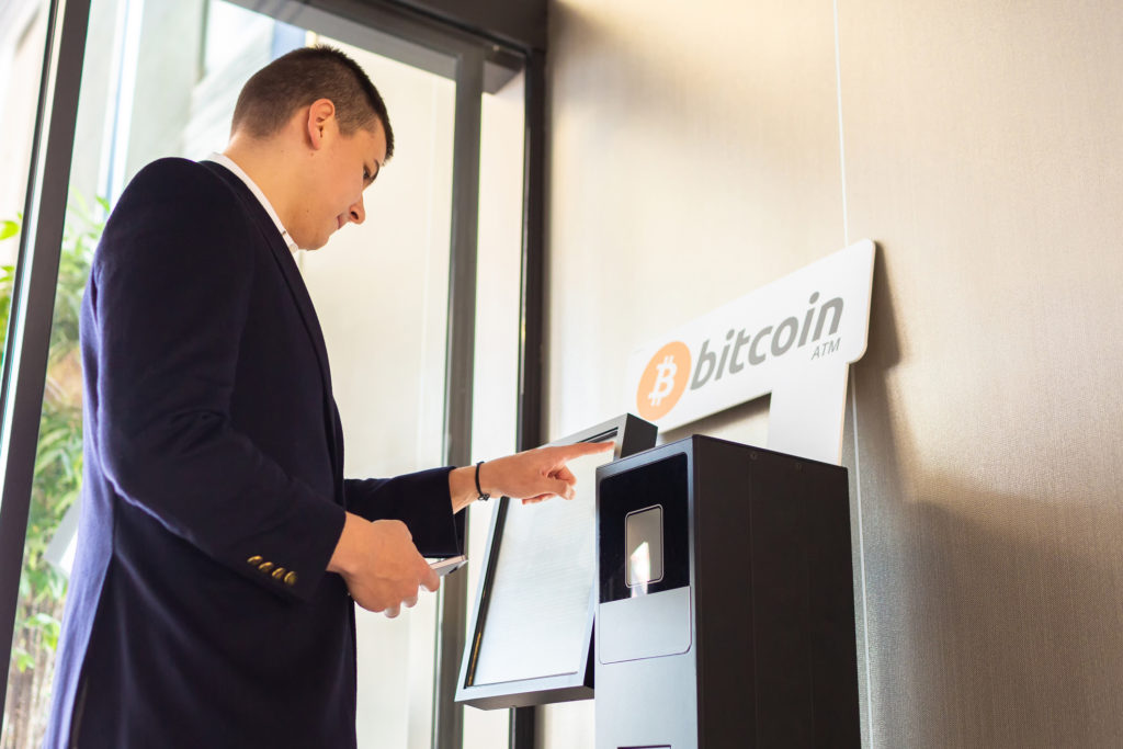 Man tapping the screen of a bitcoin atm now that he knows what backs cryptocurrency