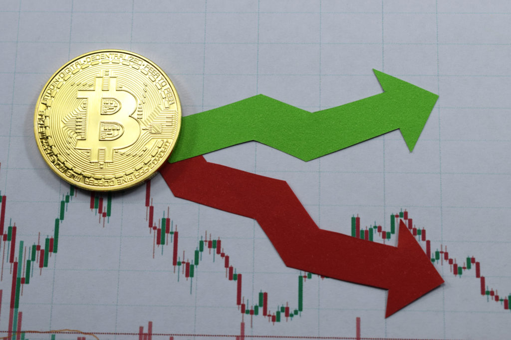 Bitcoin coin laying on price chart with green and red arrows. What backs cryptocurrency anyway?